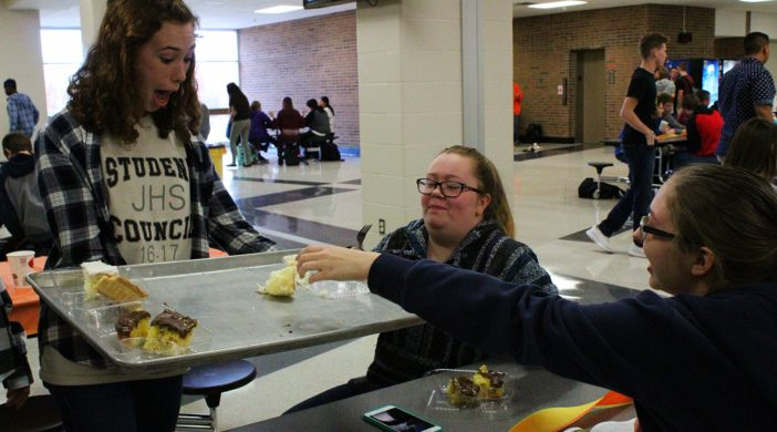 Senior Student Council member brings desserts to seniors Nicole Kress and Abby Hopf.