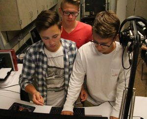 Senior Zach Johnson with juniors Max Otto and Nolan Harmon as they set up a playlist for Trap Shack. Trap Shack airs from three P.M. to four P.M. Photo by Bailey Fuhrman.