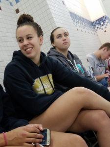 Senior Emma Hopf and freshman Madison Matheis anxiously await for the meet to start. Matheis (right) was is the first event of the morning, starting off the day with a 1000 yard freestyle. She ended up placing 11th, only two spots away from making it into finals.