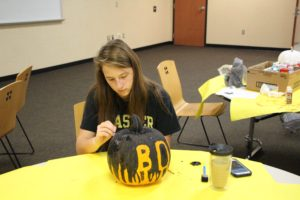 Jocelynn Morrow, Junior, focuses on painting a pumpkin to raise money for the fight against leukemia. Jocelynn had come up with a cute way to catch a donor's attention. The proceeds will go to charities to find a cure for Leukemia.