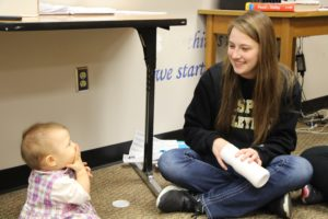 Junior Jocelynn Morrow smiles as she feeds her little cousin, a snack during first period.