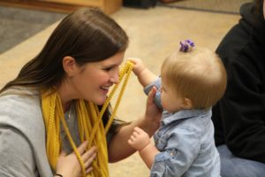 """Mrs. Beier entertains her daughter with her stringy scarf. """"...they are our future.."""" Beier has always always loved children and wants to spread her love and admiration to her students."""